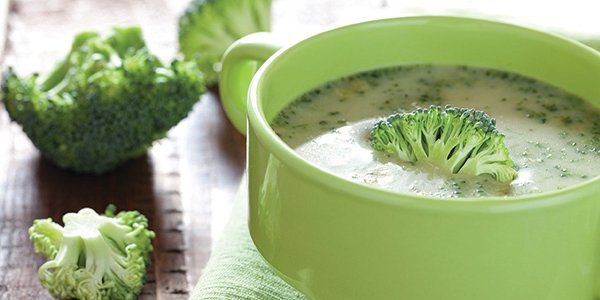 green bowl with high protein broccoli soup and broccoli garnish