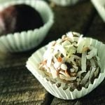photo of chocolate peanut butter protein truffles in white paper cups sitting on wooded counter