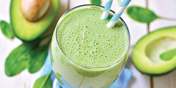 overhead photo of creamy blended green protein shake with straws in a glass